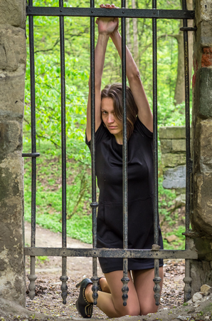 Young beautiful sexy girl prisoner behind an iron fence Stock Photo