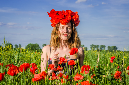 Portrait of a young beautiful girl in a poppy field with a wreath of poppies on her head on a hot summer sunny day