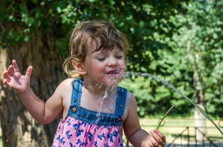 spqr: A little adorable little girl, a baby in a dress, drinking water from a spout of a Roman drinking fountain on a hot summer day, quenching thirst, in the park at Villa Pamphili in Rome