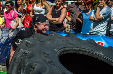 LVIV, UKRAINE - AUGUST 2017: A super strong athlete raises a huge Good Strongmen game at competitions in front of enthusiastic spectators