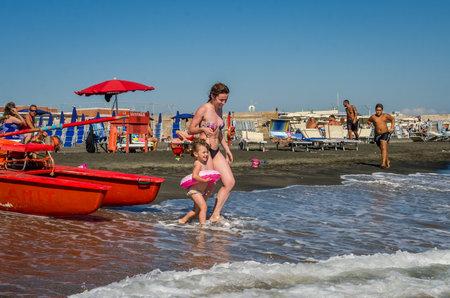 Rome, Italie - juillet 2017: Une belle jeune fille aux cheveux longs se repose sur une plage de sable, sur la côte de la mer Tyrrhénienne par une journée ensoleillée et chaude Banque d'images - 86656944