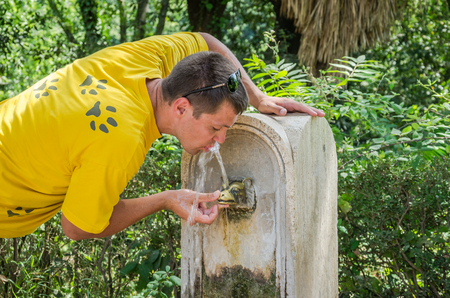 spqr: A young man drinking water, quenching thirst from an antique drinking fountain, the nose of Rome in the shape of a bronze wolf, a hot summer day in the park of the Villa Pamphili in Rome, Italy