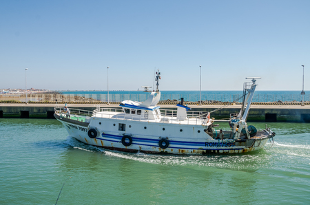 ROMA, ITALY - JULY 2017: The fishing boat comes after fishing in the port of Fiumicino on a summer sunny day