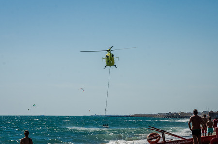 te: ROMA, ITALY - JULY 2017: A fire helicopter is picking up the water in a basket for extinguishing a fire in the Tyrrhenian Sea near Ostia, Italy