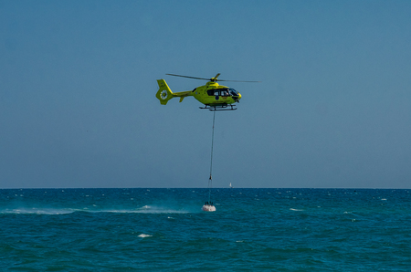 ROMA, ITALY - JULY 2017: A fire helicopter is picking up the water in a basket for extinguishing a fire in the Tyrrhenian Sea near Ostia, Italy