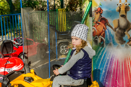 playground rides: LVIV, UKRAINE - OCTOBER 2017: Little charming girl in an amusement park on a carousel with cars