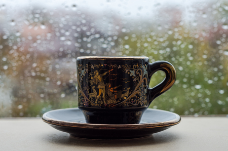 A cup of coffee on the window in the rain