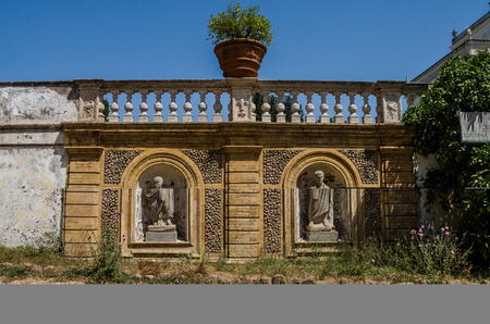 Antique statues in the fence with steps in the Villa Doria-Pamphili in Rome, Italy