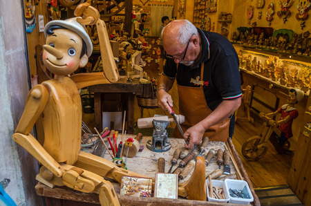 ROMA, ITALY - JULY 2017: Workshop where the master scrutinizes the handmade traditional wooden toys of Pinocchio
