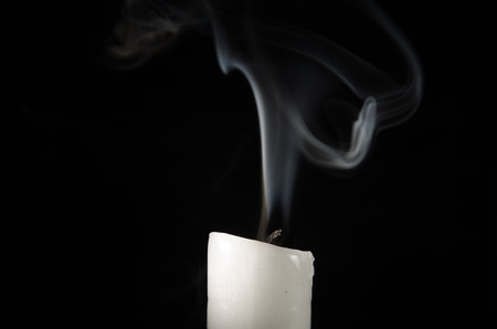 Burning candle with fading flame and smoke on a black background