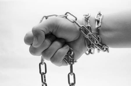Hands are chained in chains isolated on white background Stock Photo