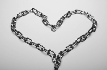 Metal heart from a chain on a white background