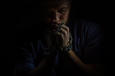 Repentant man prisoner with his hands shackled in chains on a dark background