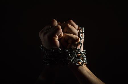 Las manos están encadenado en cadenas aisladas sobre fondo negro Foto de archivo - 94039439