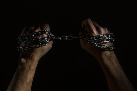 Hands are chained in chains isolated on black background Standard-Bild