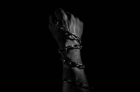 Hands are chained in chains isolated on black background Foto de archivo