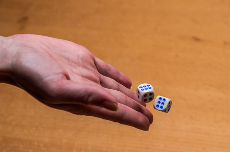 The hand throws dice to play a board game Banco de Imagens