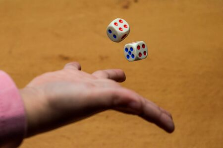 The hand throws dice to play a board game Stock Photo