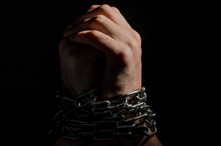 Hands are chained in chains isolated on black background Banque d'images