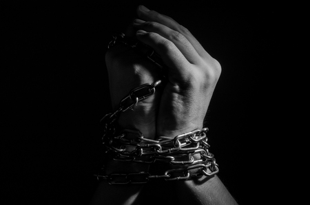 Hands are chained in chains isolated on black background Stock Photo