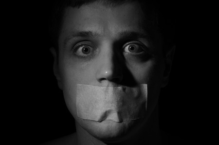 Face of a frightened man with his mouth isolated on a black background