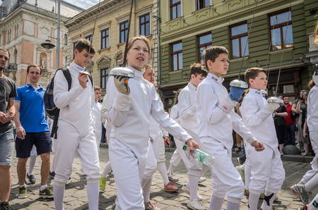 LVIV, UKRAINE - MAY 2018: Team of sportsmen in fencing goes in sports suits in the center of the city at the parade
