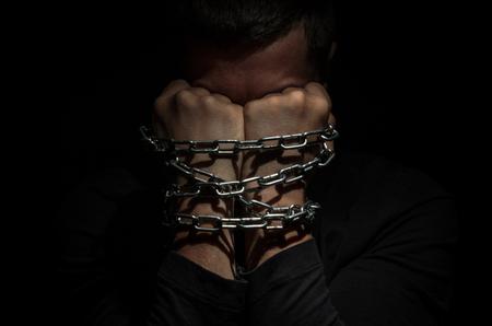 Hände gebunden in Metallketten auf einem schwarzen Hintergrund