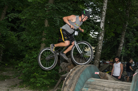 LVIV, UKRAINE - JUNE 2018: A cyclist performs tricks on a bicycle trial to overcome an obstacle course Editorial