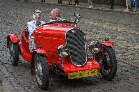 LVIV, UKRAINE - JUNE 2018: Man and woman riding a red vintage retro cabriolet car Fiat through city streets