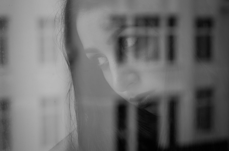 Young charming brunette girl behind a glass window Banco de Imagens