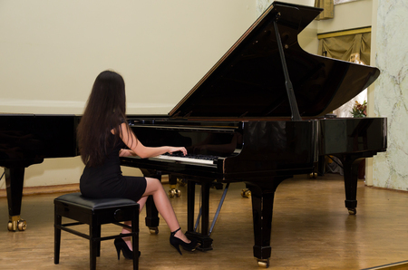 Young charming brunette girl playing the piano