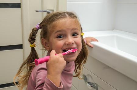 Girl child brushing her teeth