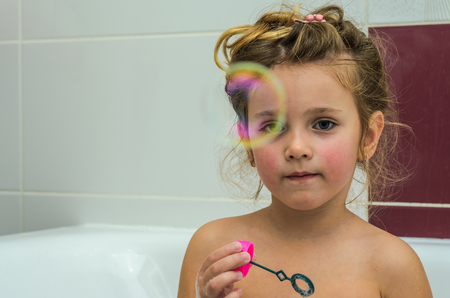Little adorable baby girl blow bubbles while bathing in the bathroom Archivio Fotografico - 112650100