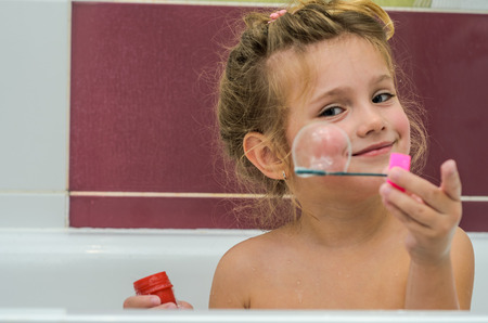 Little adorable baby girl blow bubbles while bathing in the bathroom