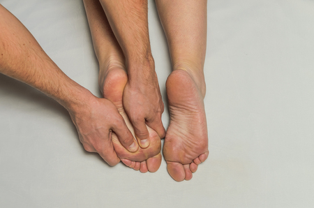 Hands massage therapist do foot massage