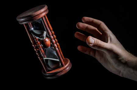 Human hands want to catch the time in the hourglass isolated on black background