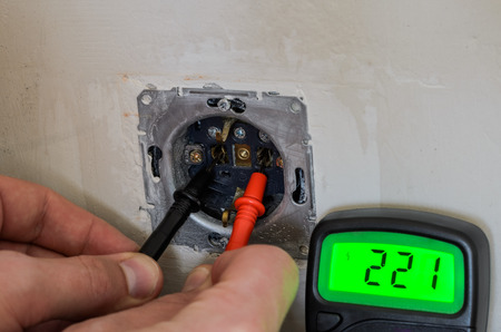 Master electrician tests the voltage in the socket with a multimeter during repair and installation