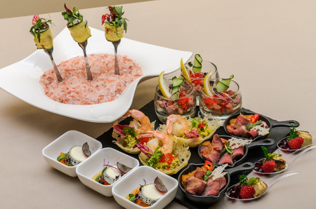 Buffet table with appetizers in a restaurant with krudite, guacamel, ceviche, bluefin, caviar, prawns and goat cheese