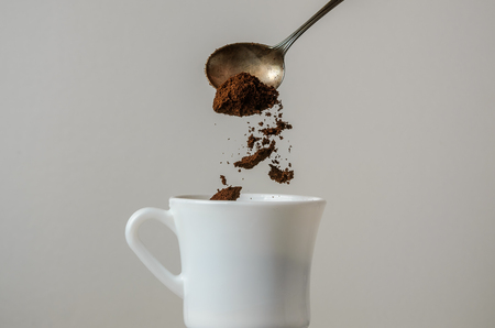 Ground coffee is poured into a white cup with a spoon