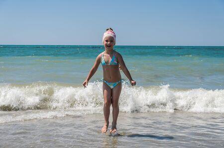 Niña encantadora juega con alegría en el mar con olas Foto de archivo