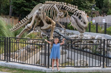 ROMA, ITALY - JULY 2019: Little charming girl child near the skeleton of a huge dinosaur in an amusement park