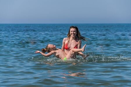 Mom and daughter play and swim in the sea, happy family Imagens