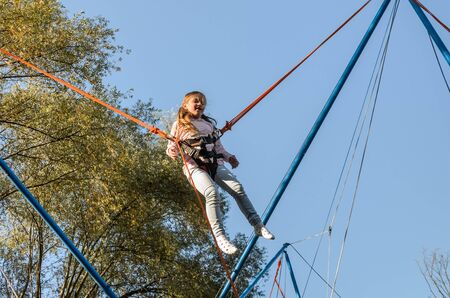 Little charming girl child on elastic ropes jumps on a trampoline in an amusement park