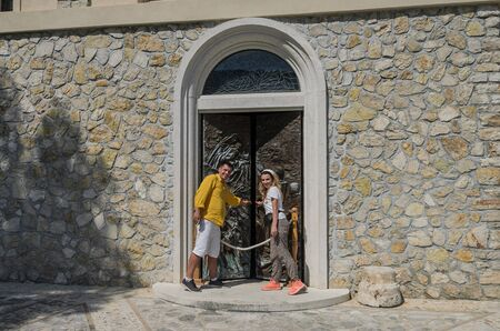 ROMA, ITALY - JULY 2019: Young family near old metal antique church doors in Greccio where St. Francis of Assisi held the first nativity scene 報道画像
