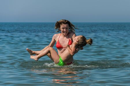 Mom and daughter play and swim in the sea, happy family Standard-Bild