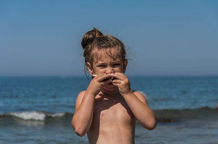 Niña encantadora comiendo coco en la playa del mar