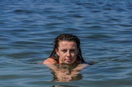 Young beautiful girl swimming in the sea
