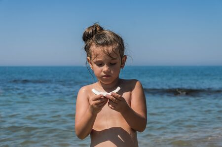 Little charming girl child eating coconut on the sea beach