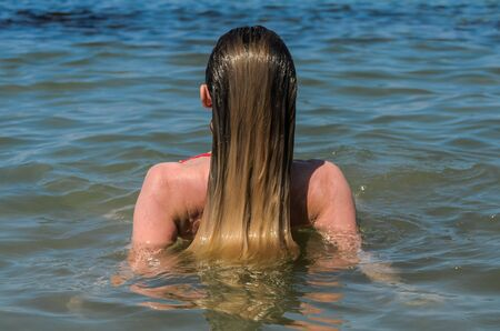 Young charming girl bathes in the sea and dries her hair in the water, rear view Imagens