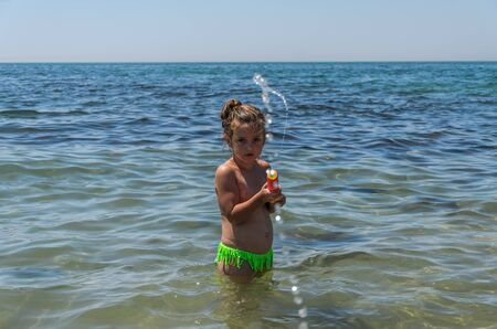 Little charming girl child plays in the sea and sprays a water gun Standard-Bild